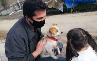 um homem e uma mulher segurando um cachorro